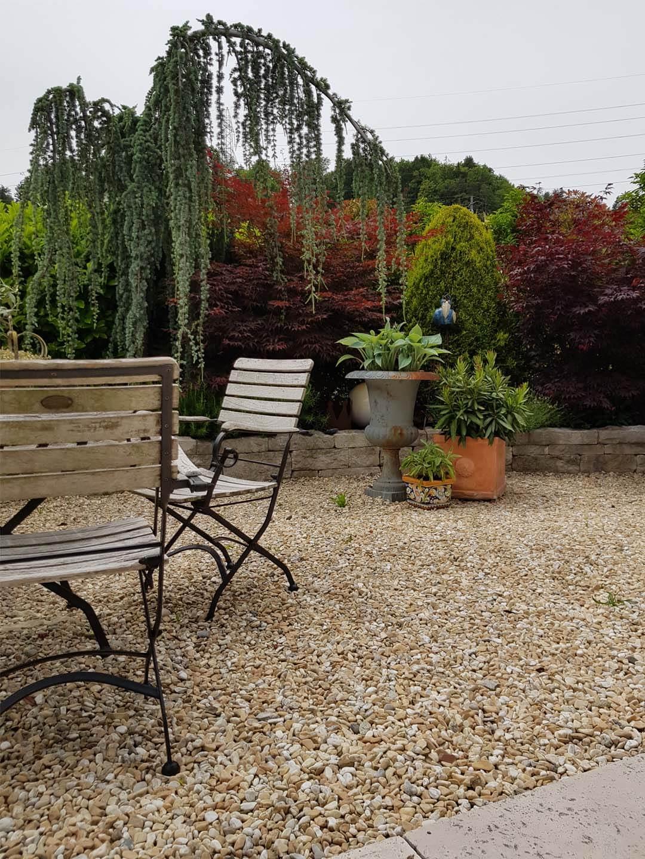 Gartensitzplatz mit Bodenbelag aus Kies, rustikalischen Stühlen und Bepflanzung im Hintergrund