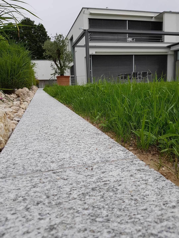 Bordsteinkante aus Granit mit grünem Rasen