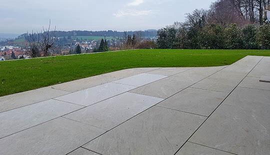 Grün-Stich Gartenbau - Gartensitzplatz mit Keramikplatten für Aussenbereich und grüner Wiese im Hintergrund