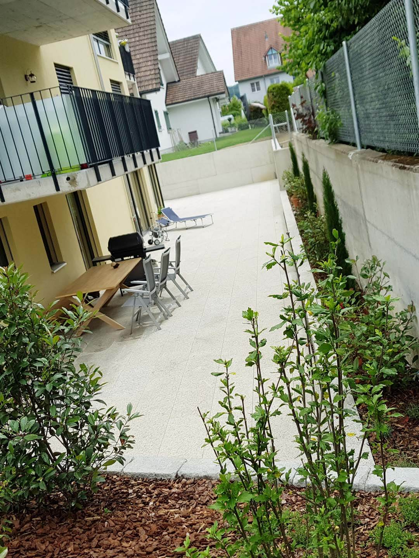 Gartensitzplatz mit Bodenplatten und Bepflanzung am Rand