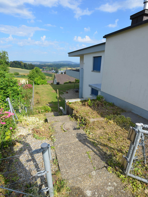 Gehweg und Treppe aus Sichtbeton, verbrannter Rasen, Gartensitzplatz aus Kies