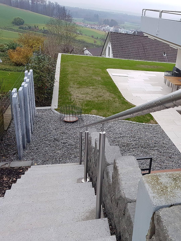 Sicht auf Treppe mit Geländer, Sichtmauer aus Granitplatten, Steingarten, Rasen und Gartensitzplatz aus Bodenplatten
