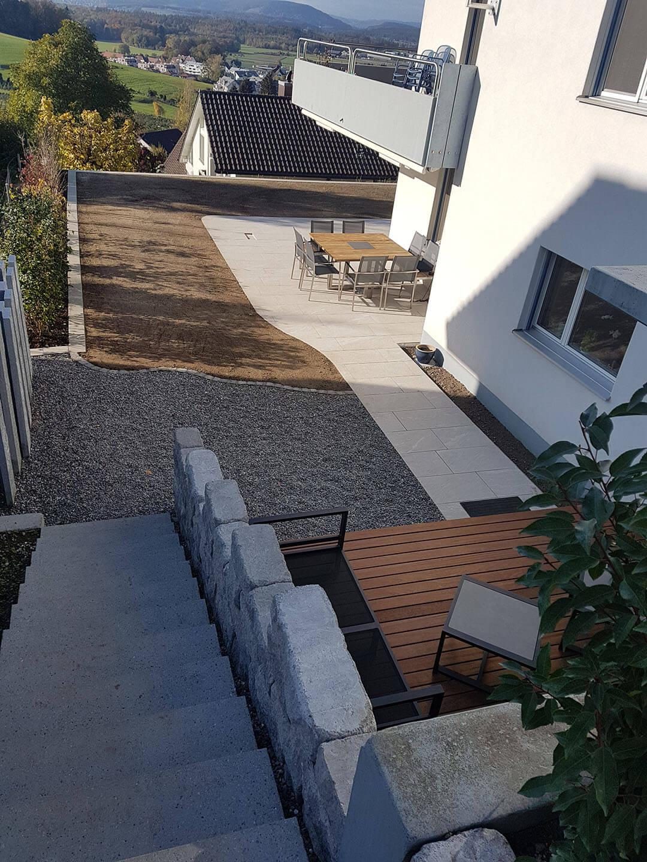 Neue Treppe aus Bettonblöcken entlang Steinmauer. Mit Aussicht auf den neuen Garten und Gartensitzplatz.