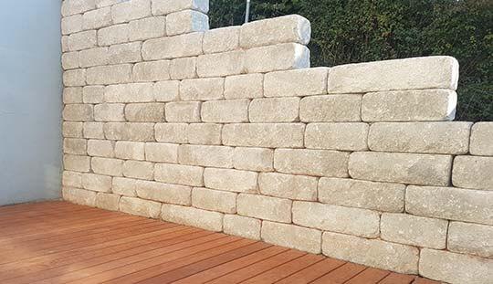 Grün-Stich Gartenbau - Betonsteinmauer beige & Holzboden im Garten
