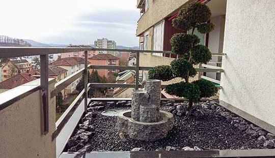 Bonsai mit Brunnen auf Steingarten auf einem Balkon